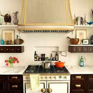 Exemple d'une cuisine éclectique avec des portes de placard en bois sombre, une crédence beige et un électroménager blanc.