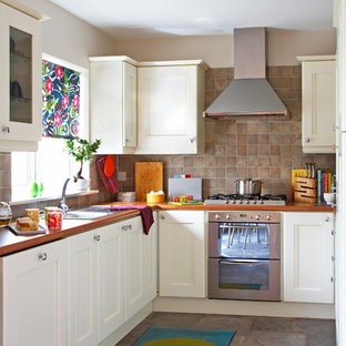 Inspiration for an eclectic separate kitchen in Dublin with a drop-in sink, recessed-panel cabinets, white cabinets, brown splashback, stainless steel appliances and slate splashback.