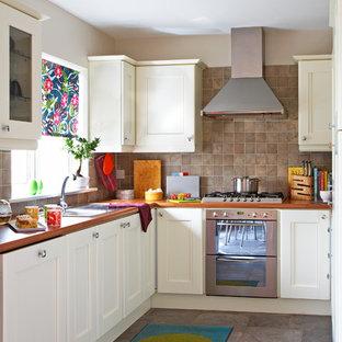 Immagine di una cucina eclettica chiusa con lavello da incasso, ante con riquadro incassato, ante bianche, paraspruzzi marrone, elettrodomestici in acciaio inossidabile e paraspruzzi in ardesia