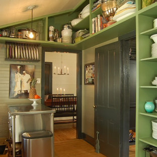 This is an example of an eclectic separate kitchen in Austin with stainless steel appliances, open cabinets, green cabinets and stainless steel benchtops.