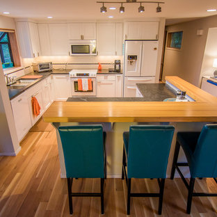 Design ideas for a mid-sized eclectic l-shaped open plan kitchen in Seattle with an undermount sink, recessed-panel cabinets, white cabinets, quartz benchtops, white splashback, ceramic splashback, white appliances, light hardwood floors and with island.