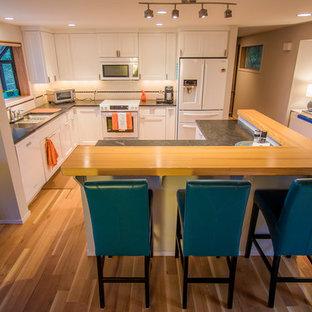 Diseño de cocina en L, ecléctica, de tamaño medio, abierta, con fregadero bajoencimera, armarios con paneles empotrados, puertas de armario blancas, encimera de cuarzo compacto, salpicadero blanco, salpicadero de azulejos de cerámica, electrodomésticos blancos, suelo de madera clara y una isla