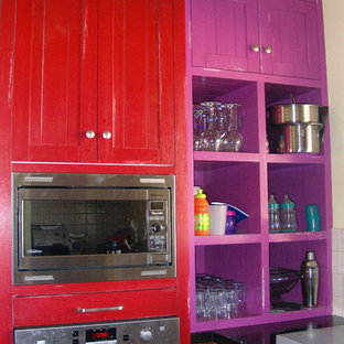 Large eclectic u-shaped kitchen pantry in Melbourne with an undermount sink, shaker cabinets, red cabinets, quartz benchtops, multi-coloured splashback, glass sheet splashback, stainless steel appliances, vinyl floors and multiple islands.