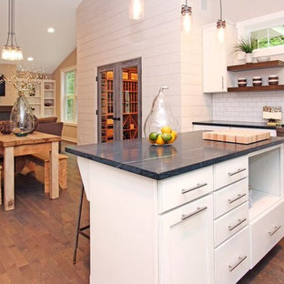 Eclectic kitchen pictures - Inspiration for an eclectic galley medium tone wood floor kitchen remodel in Grand Rapids with a farmhouse sink, raised-panel cabinets, white cabinets, soapstone countertops, white backsplash, subway tile backsplash, stainless steel appliances and an island