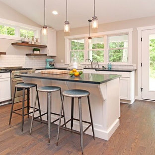 Photo of an eclectic galley kitchen in Grand Rapids with a farmhouse sink, raised-panel cabinets, white cabinets, soapstone benchtops, white splashback, subway tile splashback, stainless steel appliances, medium hardwood floors and with island.