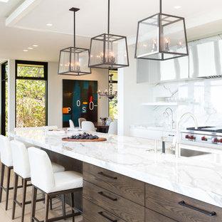 Diseño de cocina en L, contemporánea, grande, con fregadero bajoencimera, armarios estilo shaker, encimera de mármol, salpicadero blanco, salpicadero de losas de piedra, electrodomésticos de acero inoxidable, suelo de madera clara y suelo beige