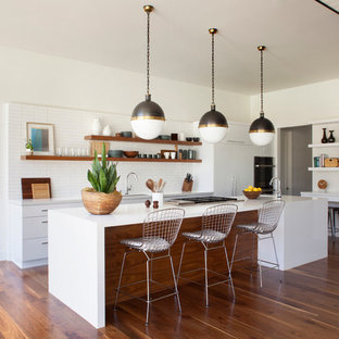 Design ideas for a mid-sized midcentury l-shaped open plan kitchen in Los Angeles with flat-panel cabinets, white cabinets, quartz benchtops, white splashback, ceramic splashback, panelled appliances, medium hardwood floors and with island.