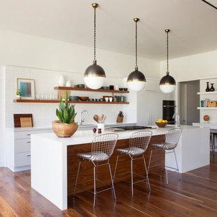 Diseño de cocina en L, retro, de tamaño medio, abierta, con armarios con paneles lisos, puertas de armario blancas, encimera de cuarzo compacto, salpicadero blanco, salpicadero de azulejos de cerámica, electrodomésticos con paneles, suelo de madera en tonos medios y una isla