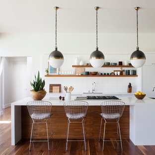 Inspiration for a mid-sized midcentury l-shaped open plan kitchen in Los Angeles with a single-bowl sink, flat-panel cabinets, white cabinets, quartz benchtops, white splashback, ceramic splashback, panelled appliances, medium hardwood floors and with island.
