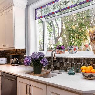 フィラデルフィアの中サイズのエクレクティックスタイルのおしゃれなキッチン (アンダーカウンターシンク、シェーカースタイル扉のキャビネット、クオーツストーンカウンター、グレーのキッチンパネル、ガラスタイルのキッチンパネル、シルバーの調理設備、濃色無垢フローリング、茶色い床、白いキャビネット) の写真