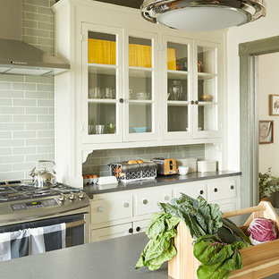 Inspiration for a mid-sized country galley eat-in kitchen in New York with a farmhouse sink, ceramic splashback, dark hardwood floors, with island, brown floor, louvered cabinets, beige cabinets, laminate benchtops, grey splashback and stainless steel appliances.