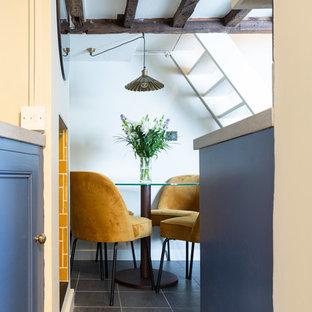 他の地域の小さいエクレクティックスタイルのおしゃれなキッチン (アンダーカウンターシンク、レイズドパネル扉のキャビネット、青いキャビネット、ラミネートカウンター、ベージュキッチンパネル、セラミックタイルのキッチンパネル、白い調理設備、スレートの床、アイランドなし、グレーの床、グレーのキッチンカウンター) の写真