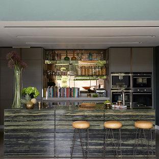 ロンドンのコンテンポラリースタイルのおしゃれなキッチン (フラットパネル扉のキャビネット、グレーのキャビネット、メタリックのキッチンパネル、ミラータイルのキッチンパネル、シルバーの調理設備の、コンクリートの床、緑のキッチンカウンター) の写真