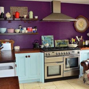 Photo of a mid-sized country l-shaped eat-in kitchen in Wiltshire with a drop-in sink, shaker cabinets, blue cabinets, wood benchtops, stainless steel appliances, ceramic floors, no island and beige floor.