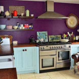 ウィルトシャーの中サイズのカントリー風おしゃれなキッチン (ドロップインシンク、シェーカースタイル扉のキャビネット、青いキャビネット、木材カウンター、シルバーの調理設備の、セラミックタイルの床、アイランドなし、ベージュの床) の写真