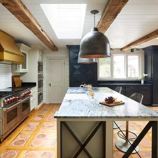ナッシュビルのエクレクティックスタイルのおしゃれなキッチン (エプロンフロントシンク、落し込みパネル扉のキャビネット、白いキャビネット、白いキッチンパネル、シルバーの調理設備、テラコッタタイルの床、オレンジの床) の写真