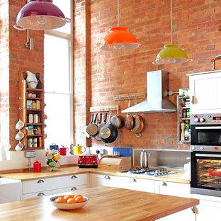 ロンドンの中サイズのエクレクティックスタイルのおしゃれなキッチン (シェーカースタイル扉のキャビネット、白いキャビネット、木材カウンター、メタリックのキッチンパネル、シルバーの調理設備の) の写真