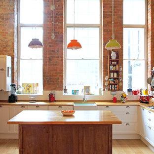 Foto på ett mellanstort eklektiskt kök, med luckor med infälld panel, vita skåp, träbänkskiva, stänkskydd med metallisk yta, rostfria vitvaror och en köksö