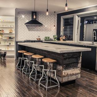 Réalisation d'une grande cuisine ouverte bohème avec un évier 2 bacs, un plan de travail en béton, une crédence blanche, une crédence en carrelage métro, un sol en bois foncé et un îlot central.