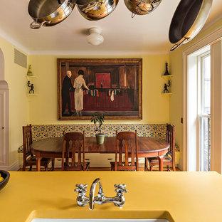Foto di una cucina tradizionale di medie dimensioni con lavello stile country, ante in stile shaker, ante gialle, top in vetro riciclato, paraspruzzi bianco, paraspruzzi con piastrelle in ceramica, elettrodomestici colorati, pavimento in legno massello medio, isola e pavimento arancione
