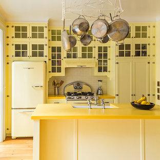 Diseño de cocina tradicional, de tamaño medio, con puertas de armario amarillas, encimera de vidrio reciclado, salpicadero blanco, electrodomésticos de colores, una isla, armarios tipo vitrina, salpicadero de azulejos tipo metro, suelo de madera clara y encimeras amarillas