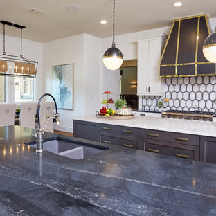 This is an example of a mid-sized eclectic l-shaped eat-in kitchen in Dallas with a double-bowl sink, shaker cabinets, white cabinets, marble benchtops, white splashback, porcelain splashback, stainless steel appliances, medium hardwood floors and multiple islands.