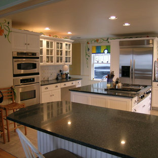 Photo of a large country u-shaped eat-in kitchen in Portland Maine with an undermount sink, louvered cabinets, white cabinets, white splashback, porcelain splashback, stainless steel appliances, ceramic floors, with island and granite benchtops.