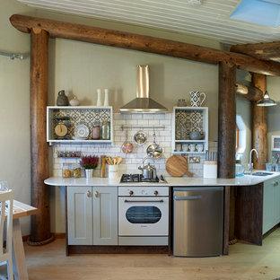 Einzeilige, Kleine Rustikale Küche ohne Insel mit Unterbauwaschbecken, Schrankfronten im Shaker-Stil, grauen Schränken, Küchenrückwand in Weiß, Rückwand aus Metrofliesen, weißen Elektrogeräten und braunem Holzboden in Sonstige