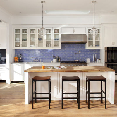 Trendy kitchen photo in San Francisco with glass-front cabinets, paneled appliances, a farmhouse sink, wood countertops, white cabinets, blue backsplash and subway tile backsplash