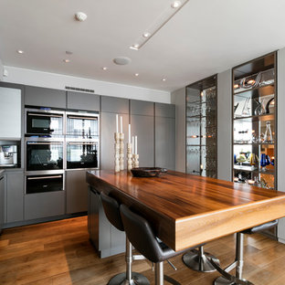 Design ideas for a midcentury l-shaped open plan kitchen in London with a double-bowl sink, flat-panel cabinets, grey cabinets, dark hardwood floors and with island.