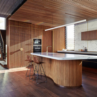 This is an example of a midcentury kitchen in Perth with a single-bowl sink, flat-panel cabinets, black cabinets, white splashback, dark hardwood floors, with island, brown floor, grey benchtop and panelled appliances.