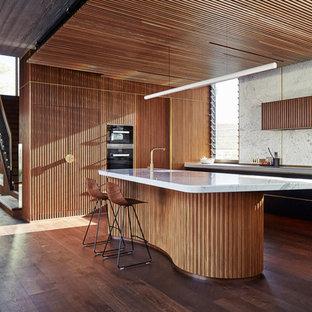 Foto di una cucina minimalista con lavello a vasca singola, ante lisce, ante nere, paraspruzzi bianco, parquet scuro, isola, pavimento marrone, top grigio e elettrodomestici da incasso