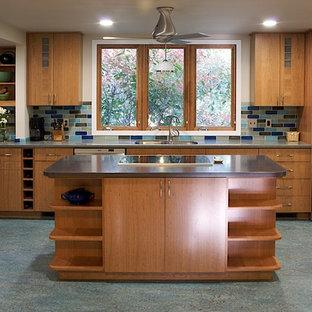 Réalisation d'une cuisine américaine tradition avec un évier encastré, un placard à porte plane, des portes de placard en bois brun, une crédence multicolore, un électroménager en acier inoxydable et un sol turquoise.