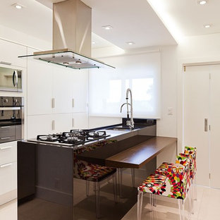 Photo of a mid-sized contemporary u-shaped eat-in kitchen in Other with a drop-in sink, flat-panel cabinets, white cabinets, quartzite benchtops, black splashback, limestone splashback, stainless steel appliances, ceramic floors, multiple islands and grey floor.