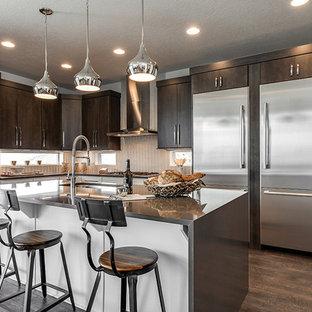 Inredning av ett klassiskt mellanstort kök, med en undermonterad diskho, släta luckor, bruna skåp, bänkskiva i onyx, vitt stänkskydd, stänkskydd i glaskakel, rostfria vitvaror, laminatgolv, en köksö och brunt golv