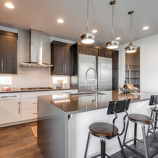 Bild på ett mellanstort vintage kök, med en undermonterad diskho, släta luckor, vita skåp, bänkskiva i onyx, vitt stänkskydd, stänkskydd i glaskakel, rostfria vitvaror, laminatgolv, en köksö och brunt golv