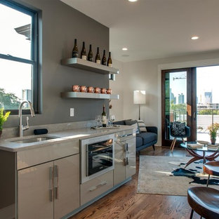 Contemporary open concept kitchen ideas - Open concept kitchen - contemporary single-wall medium tone wood floor and brown floor open concept kitchen idea in Nashville with an undermount sink, flat-panel cabinets, beige cabinets, gray backsplash and beige countertops