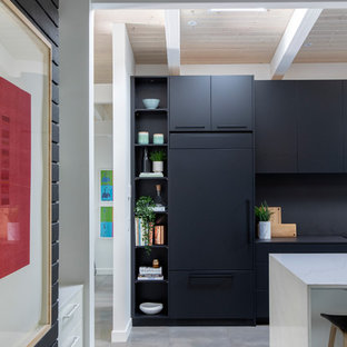 Large midcentury single-wall open plan kitchen in Vancouver with flat-panel cabinets, black cabinets, quartz benchtops, black splashback, with island, grey floor, an undermount sink, panelled appliances, concrete floors and black benchtop.