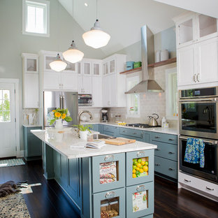 Large traditional l-shaped kitchen in Other with shaker cabinets, white cabinets, subway tile splashback, stainless steel appliances, with island, brown floor, a farmhouse sink, quartzite benchtops, grey splashback and bamboo floors.