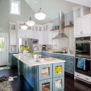 Modelo de cocina en L, clásica, grande, con armarios estilo shaker, puertas de armario blancas, salpicadero de azulejos tipo metro, electrodomésticos de acero inoxidable, una isla, suelo marrón, fregadero sobremueble, encimera de cuarcita, salpicadero verde y suelo de bambú