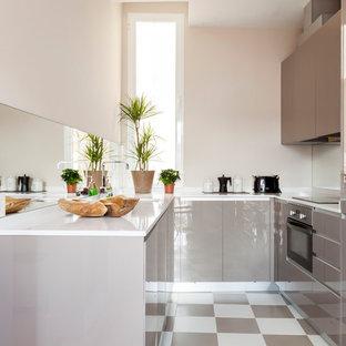 Imagen de cocina en U, actual, pequeña, cerrada, sin isla, con armarios con paneles lisos, puertas de armario blancas, salpicadero con efecto espejo y suelo multicolor