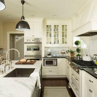 На фото: кухня в классическом стиле с врезной раковиной, стеклянными фасадами, белыми фасадами, белым фартуком, фартуком из плитки кабанчик, техникой из нержавеющей стали, темным паркетным полом и островом с