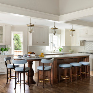 Elegant l-shaped dark wood floor and brown floor kitchen photo in Minneapolis with raised-panel cabinets, white cabinets, white backsplash, subway tile backsplash, an island and white countertops