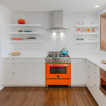 Eye-Popping Orange Range Warms Up a Sleek White Kitchen