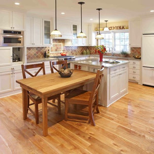 Mid-sized traditional eat-in kitchen designs - Mid-sized elegant l-shaped light wood floor eat-in kitchen photo in Minneapolis with stainless steel appliances, an island, flat-panel cabinets, white cabinets, multicolored backsplash, terra-cotta backsplash, an undermount sink and granite countertops