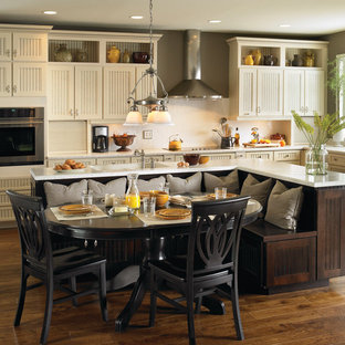 Design ideas for a mid-sized victorian l-shaped eat-in kitchen in Dallas with an undermount sink, louvered cabinets, white cabinets, granite benchtops, white splashback, subway tile splashback, dark hardwood floors, with island and brown floor.