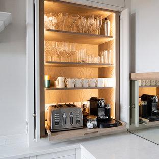 エディンバラの大きいエクレクティックスタイルのおしゃれなキッチン (エプロンフロントシンク、インセット扉のキャビネット、白いキャビネット、珪岩カウンター、ミラータイルのキッチンパネル、シルバーの調理設備の、ベージュの床、白いキッチンカウンター) の写真