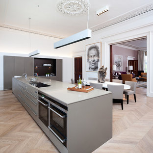 This is an example of a large contemporary kitchen/diner in Edinburgh with flat-panel cabinets, grey cabinets, light hardwood flooring and an island.