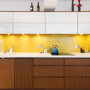 Imagen de cocina lineal, actual, con armarios con paneles lisos, puertas de armario de madera oscura y salpicadero amarillo