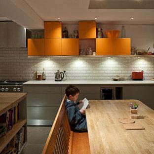 Mittelgroße Moderne Wohnküche in L-Form mit flächenbündigen Schrankfronten, orangefarbenen Schränken, Granit-Arbeitsplatte, Küchenrückwand in Gelb, Rückwand aus Keramikfliesen, Küchengeräten aus Edelstahl, Keramikboden und Kücheninsel in London